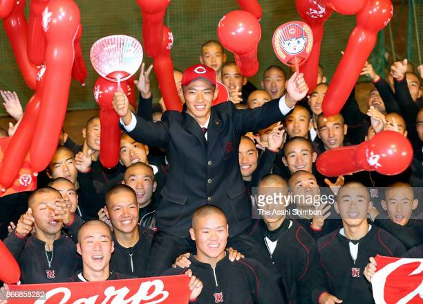 Shosei Nakamura of Koryo High School poses for photographs with his team mates after picked up by Hiroshima Toyo Carp after the 2017 professional...