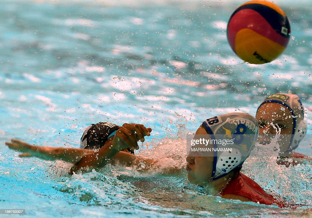 A shot at goal from Angelina Djumalieva (C) of Uzbekistan is blocked by Belore Shraddha of India (L) during their water polo match at the 9th Asian Swimming Championships in Dubai, on November 20, 2012.