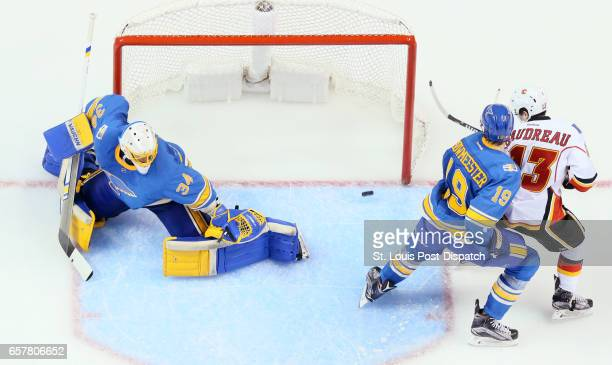 A shot by Calgary Flames defenseman Matt Bartkowski not pictured goes in off the left skate of St Louis Blues defenseman Jay Bouwmeester past...