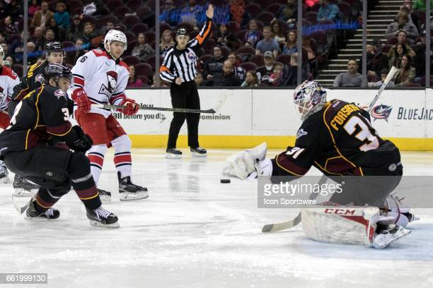 A shot by Charlotte Checkers LW Sergey Tolchinsky goes off the glove of Cleveland Monsters G Anton Forsberg during the third period of the AHL hockey...