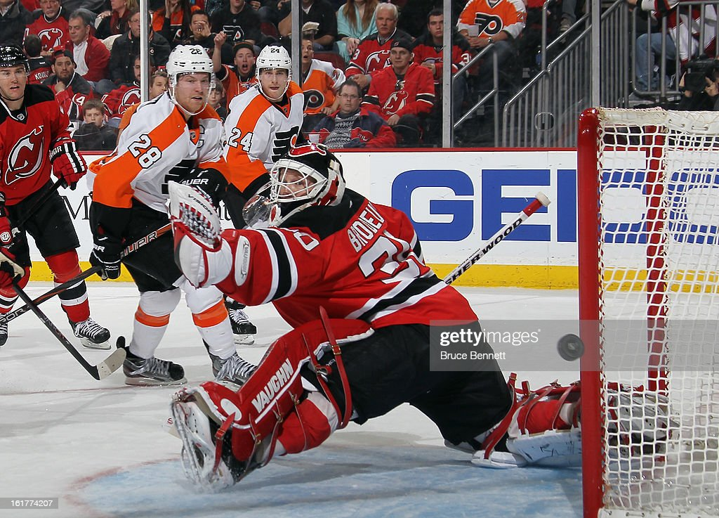 A shot by Claude Giroux #28 of the Philadelphia Flyers is deflected by Martin Brodeur #30 of the New Jersey Devils in the third period at the Prudential Center on February 15, 2013 in Newark, New Jersey. The Devils defeated the Flyers 5-3.