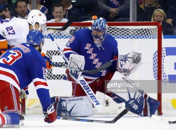 A shot by Mathew Barzal of the New York Islanders hits the shoulder of Henrik Lundqvist of the New York Rangers during the third period at Madison...
