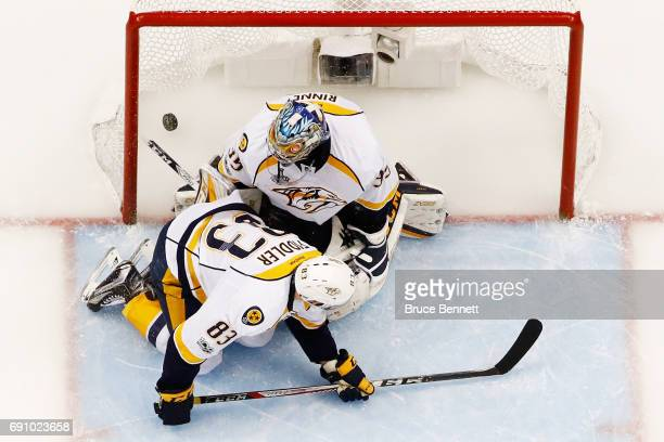 A shot by Scott Wilson of the Pittsburgh Penguins bounces off of Vernon Fiddler and past Pekka Rinne of the Nashville Predators for a goal during the...