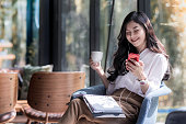 Shot of a beautiful young asian woman holding cup of coffee and listening  music from her phone in the coffee shop
