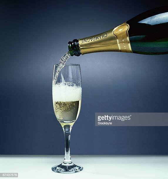 shot of a champagne poured from a bottle into a champagne glass