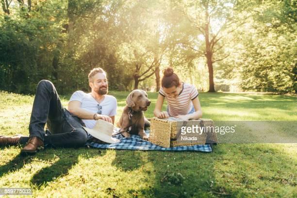 Schuss von glücklicher Vater mit Tochter im Teenageralter und Hund liegend auf einer Decke in einem park