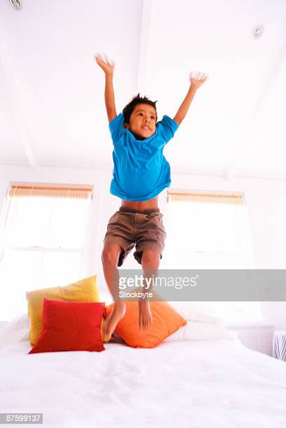 shot of a young boy (6-8) jumping on a bed with his arms raised