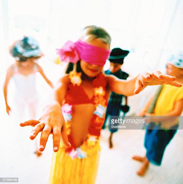 shot of a young girl in a costume blind folded