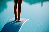 A person standing on a diving board.  Only the back of the person's legs and feet are visible.  The person is standing up straight.  There's a light reflecting off of the person's feet and the top of