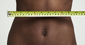 Shot of black female waist with measuring tape