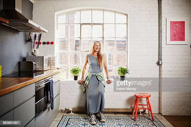A shot of funky older woman standing in kitchen