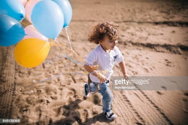 Schuss von fröhlicher Junge laufen am Strand mit Ballons