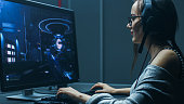 Shot of the Beautiful Professional Gamer Girl Playing in First-Person Shooter Online Video Game on Her Personal Computer. Casual Cute Geek wearing Glasses and Talking into Headset. In the Basement Gam