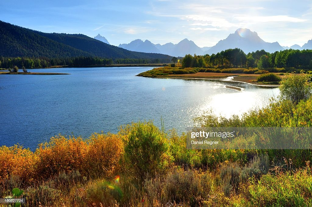 CONTENT] A shot of the Grand Teton National Park, with a lake in the foreground, a beautiful sunlight coming across the shrubbery and tall mountain peaks in the distance.