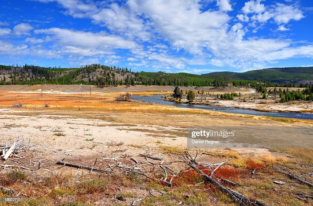 CONTENT] A shot of the landscape of Yellowstone National Park, on a partly cloudy summer day. The hot springs and sulphates in the soil can be seen with the redness of the ground.