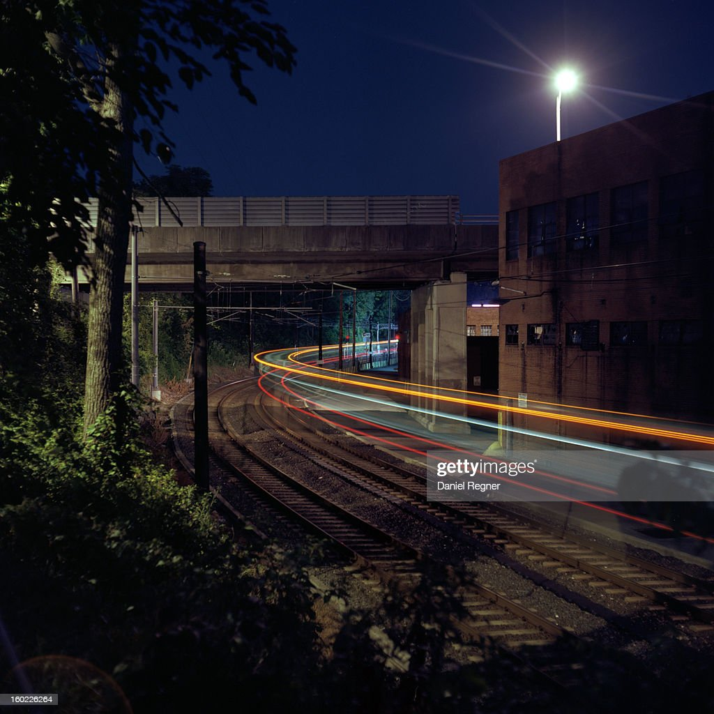 CONTENT] A shot of the lightrail coming through Baltimore at night. The light streams of the train can be seen going northbound, traveling through from one place to another. It is nighttime, late evening.