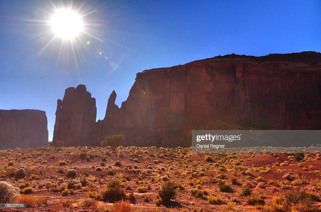 CONTENT] A shot of the sun blazing down on Monument Valley. An HDR image that shows all the levels of the heat, and hot red sands of Monument Valley, Utah.