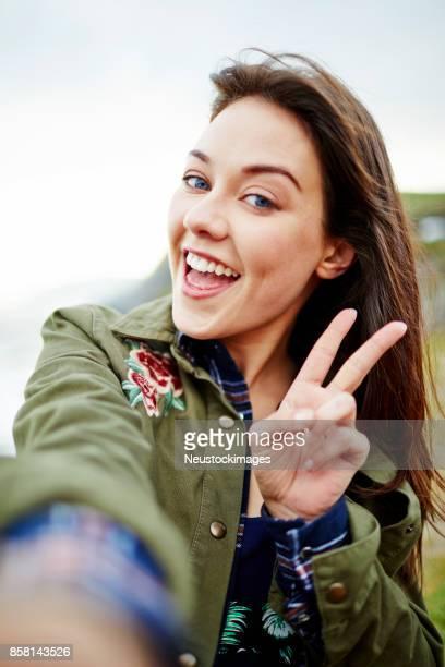 POV shot of woman smiling while taking selfie on mountain