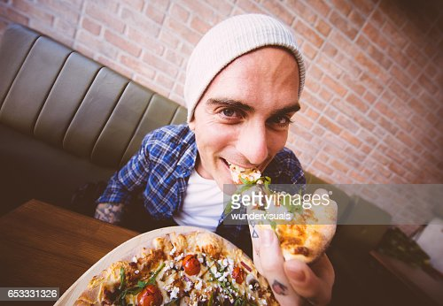 Shot of young man biting a slice of pizza : Photo