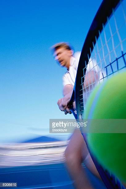 Shot up racket of man hitting ball