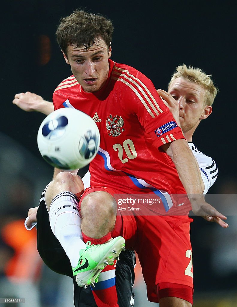 Shota Bibilov (front) of Russia is challenged by <a gi-track='captionPersonalityLinkClicked' href=/galleries/search?phrase=Patrick+Funk&family=editorial&specificpeople=691617 ng-click='$event.stopPropagation()'>Patrick Funk</a> of Germany during the UEFA European U21 Championship Group B match between Russia and Germany at Netanya Stadium on June 12, 2013 in Netanya, Israel.