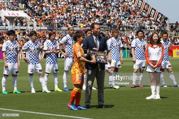 Shota Kaneko of Shimizu SPulse reaceives the shield of the JLeague J1's 20000th goal by JLeague vice chairman Hiromi Hara prior to the JLeague J1...
