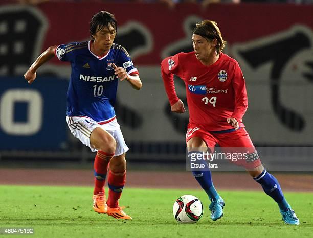 Shota Kawanishi of Montedio Yamagata and Shunsuke Nakamura of Yokohama FMarinos compete for the ball during the JLeague match between Yokohama...