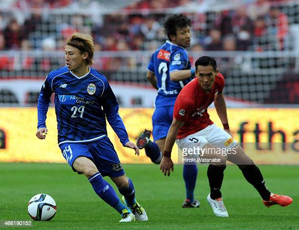 Shota Kawanishi of Montedio Yamagata and Tomoaki Makino of Urawa Red Diamonds compete for the ball during the JLeague match between Urawa Red...