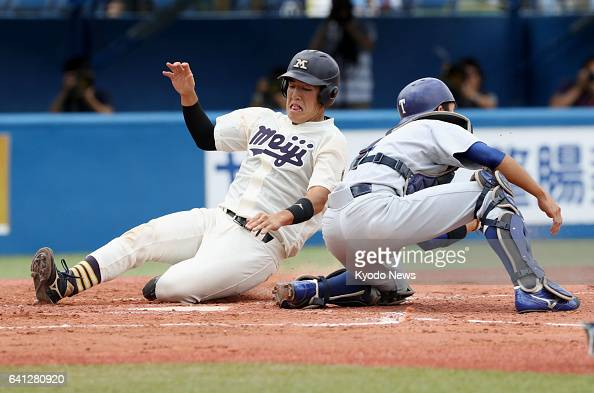 Shota Ushijima of Meiji slides safely into the home base away from the tag of Tomohiro Kiire of Tokyo in the second inning during the Tokyo ig6...