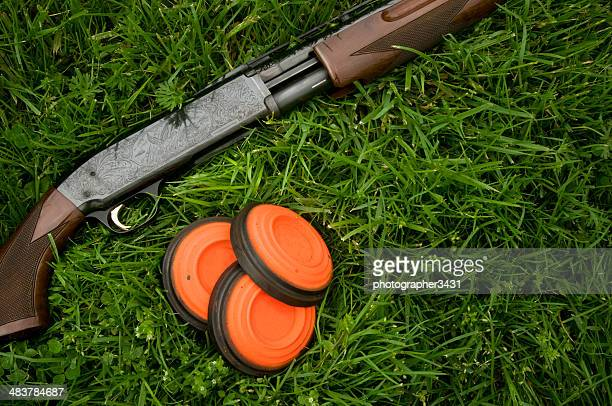 Shotgun and clay pigeons laying in grass
