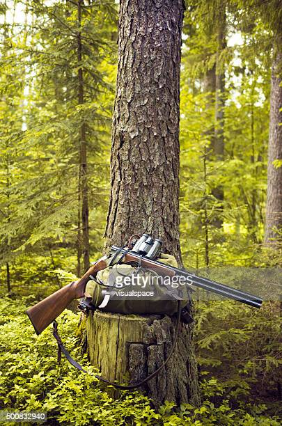 Shotgun, Binoculars and Backpack in a Forest Environment