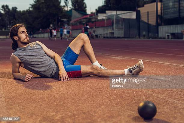 Shout put athlete relaxing on a stadium and looking away.