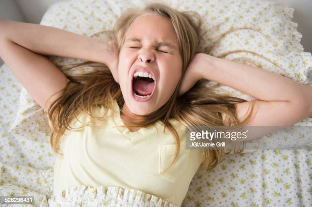 Shouting Caucasian girl covering her ears on bed