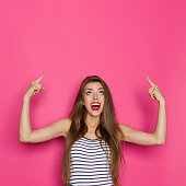 Shouting beautiful young woman in striped shirt looking up and pointing. Waist up studio shot on pink background.