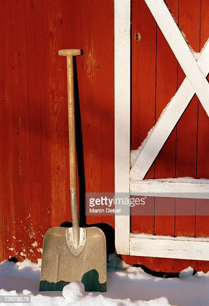 Shovel against a red wooden house