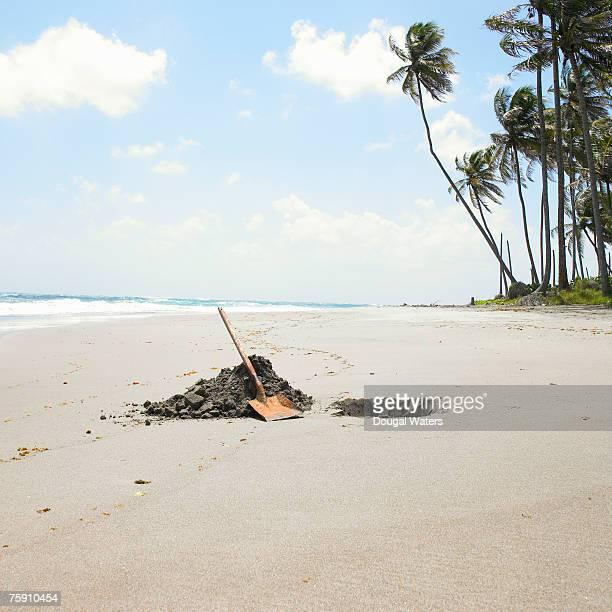 Shovel and hole on beach