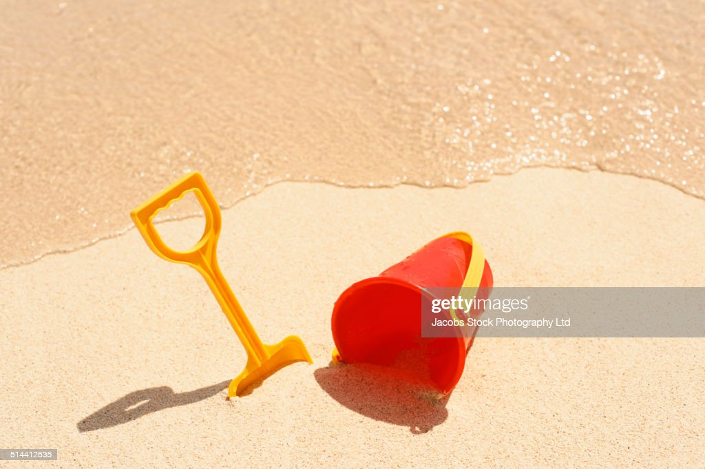 Shovel and pail on sand at beach