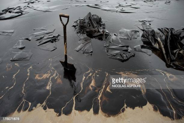 A shovel sits in oilcovered sand at Ao Phrao beach as volunteers work to clean up the area after a major oil slick hit the island of Ko Samet on July...