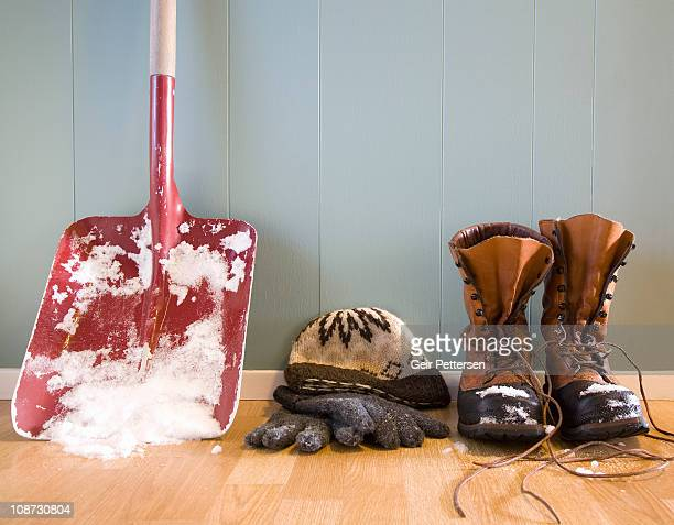 Shovel with snow, winter boots, hat and gloves