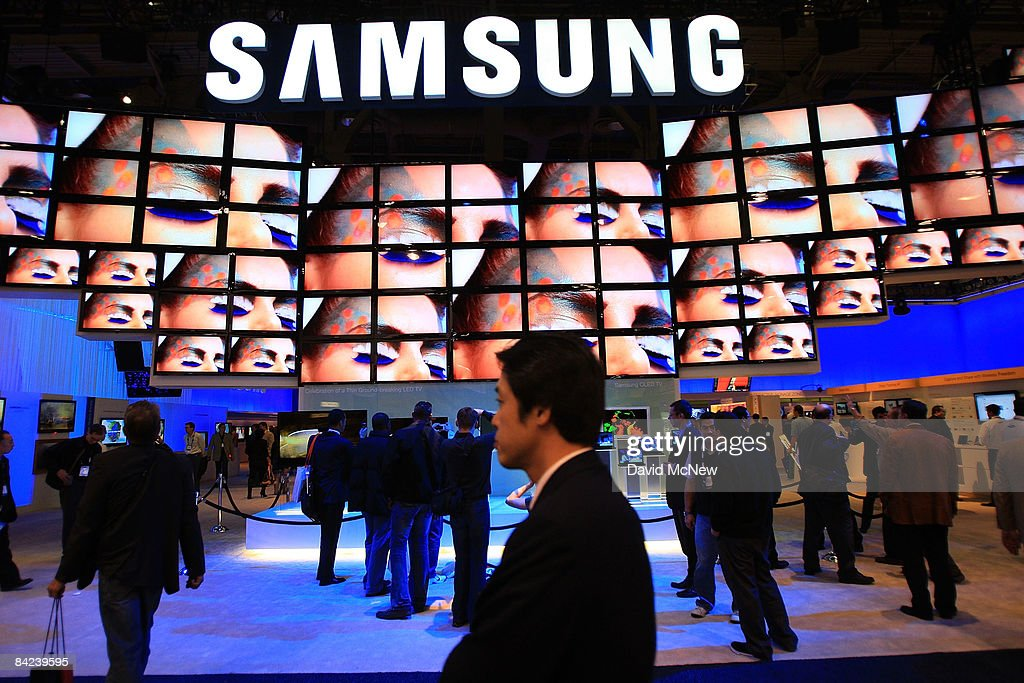 Show attendees watch a flatscreen television display at the Samsung booth at the Las Vegas Convention Center during the 2009 International Consumer...