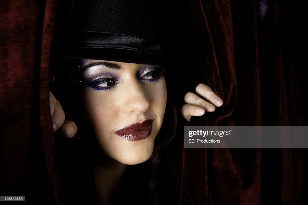 Show Girl Looking Through Dark Red Curtain