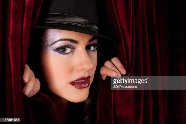 Show Girl Peeking Through Dark Red Curtain
