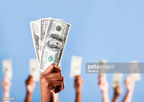 Show me the money! Many hands holding up US dollars