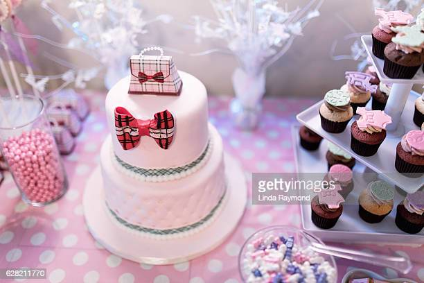 shower cake, cup cakes and candies on a table