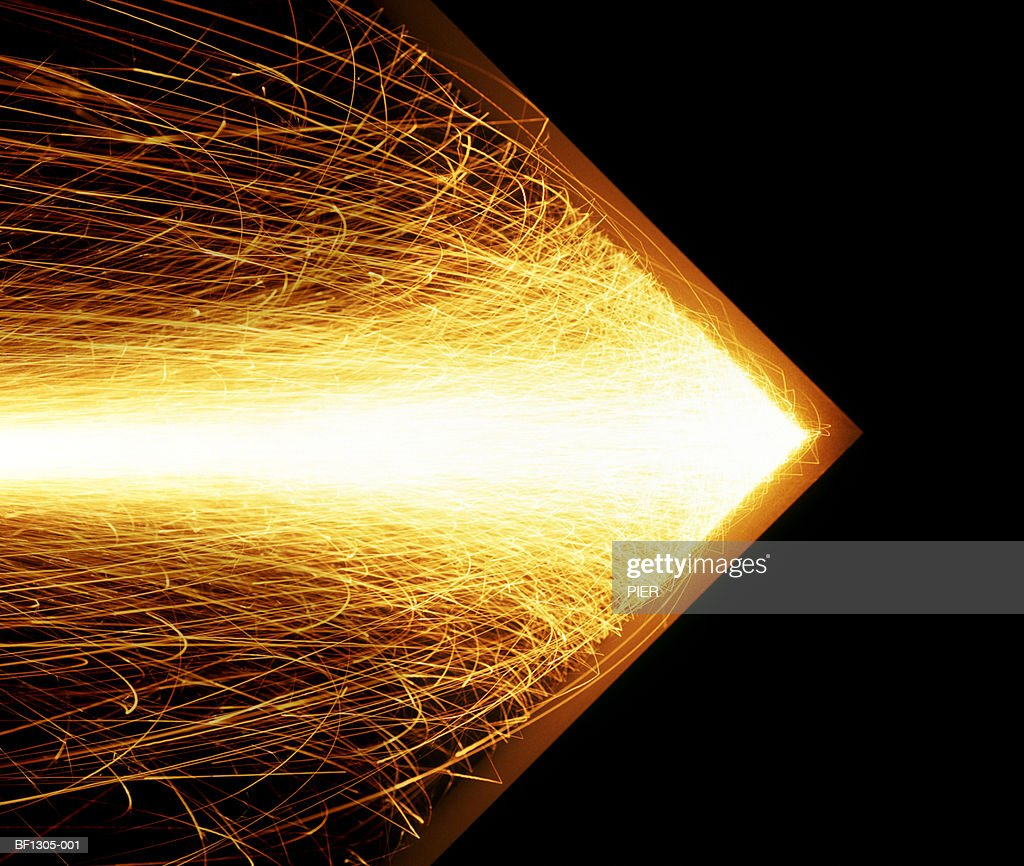 Shower of sparks hitting metal to form arrow shape