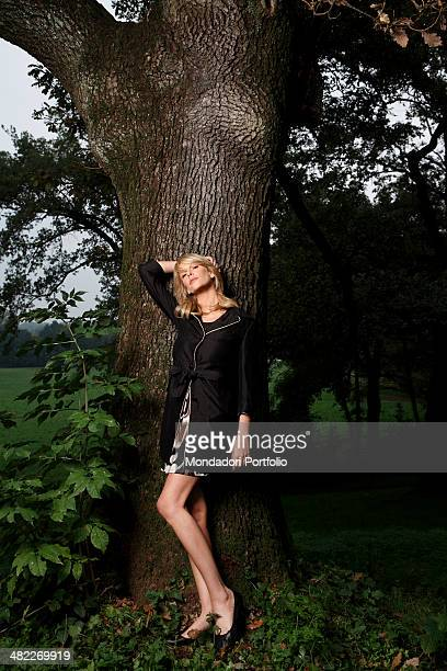 Showgirl Alessia Marcuzzi poses in front of a tree during a photo shoot on the set of Vous les femmes in 2008 at Villa Rapazzini Arcore Italy