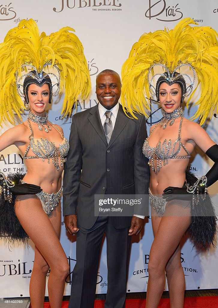 Showgirl Brittany Guinane, former Olympian Carl Lewis and showgirl Taryn Olivieri arrive at the 'Jubilee!' show's grand reopening at Ballys Las Vegas on March 29, 2014 in Las Vegas, Nevada.