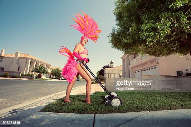 Showgirl mowing lawn