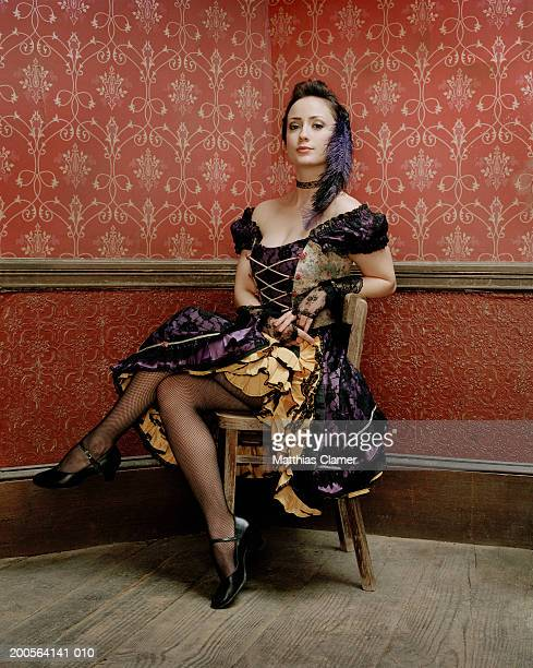 Showgirl sitting on chair, smiling, portrait