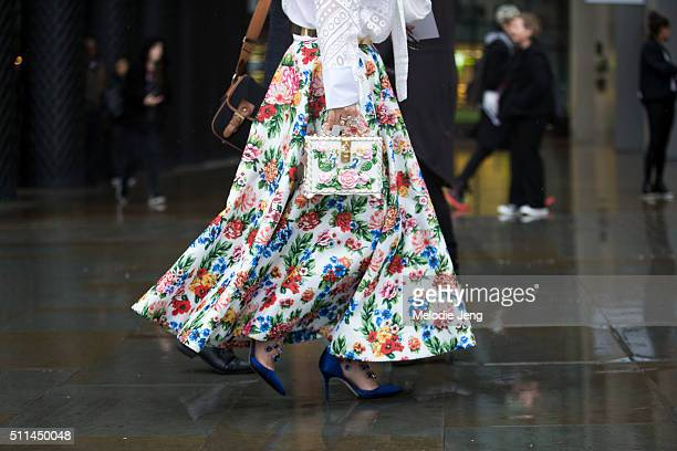 A showgoer wears a floral skirt and purse during London Fashion Week Autumn/Winter 2016/17 at the Emilia Wickstead show on February 20 2016 in London...
